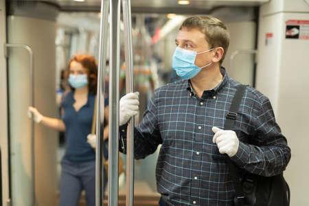 Man in medical mask riding in subway car