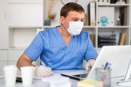 Man doctor in face mask working at laptop