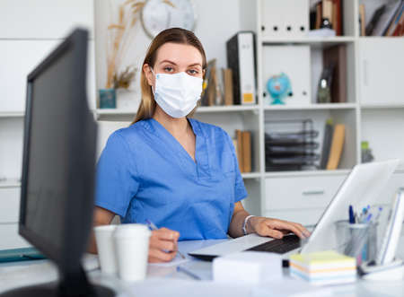 Woman doctor in face mask working on laptop