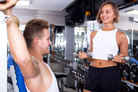 Woman training hands using weight dumbbells