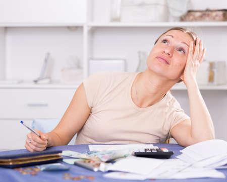 Upset woman calculating finances 写真素材