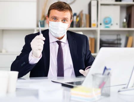 Businessman in medical mask and gloves holding meeting in office