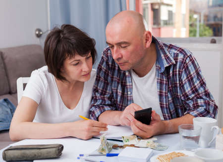 Mature couple with phone calculation money sitting at table
