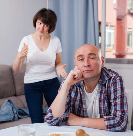 Upset mature man sitting while quarrel with wife at home interior