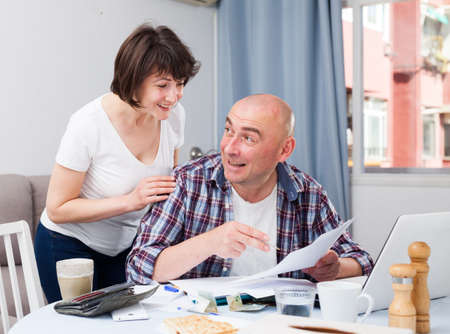 Husband and wife with financial documents near laptop