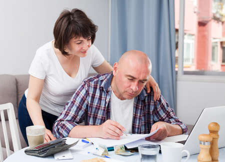 Mature couple with financial documents in home interior