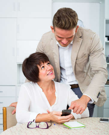 Son telling adult mother how to use phone