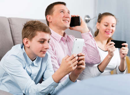 Parents and son using phones