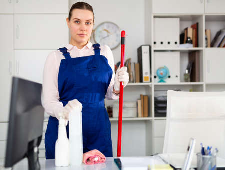 Smiling woman in uniform making cleaning in the office