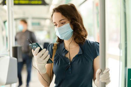 Brunette in medical mask listening to music in city bus