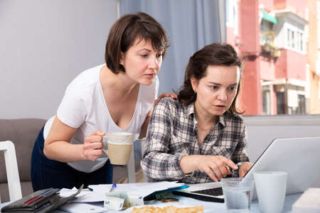 Women working with documents while working at laptop at home