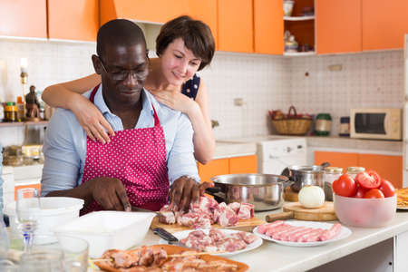 Cheerful international couple cooking