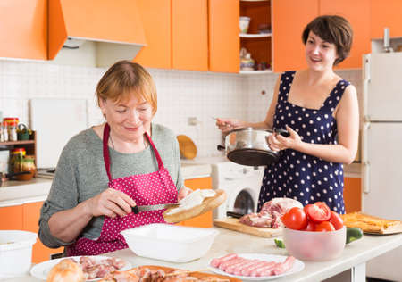 Senior woman and her daughter-in-law preparing dinner