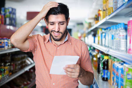 Adult male customer is looking in note in supermarket