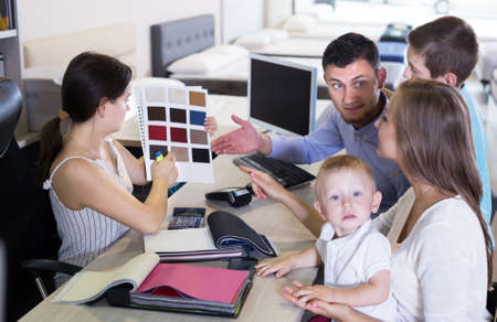 saleswoman in furniture store helping young family in choice of mattress material