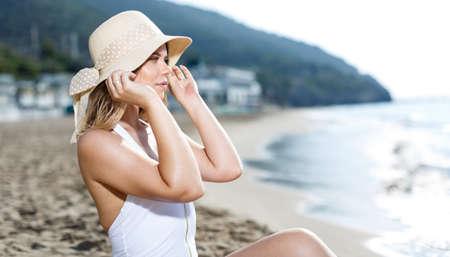 Cheerful sexy girl in swimsuit taking sunbath at sandy beach 免版税图像