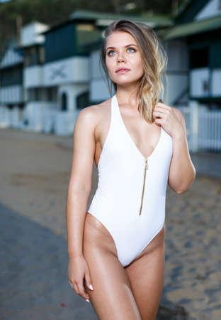 Sexy girl in swimsuit posing near buildings at sea shore 免版税图像 - 157801607