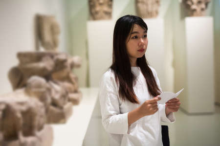 Chinese girl with interest using guidebook at ancient sculptures