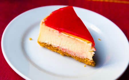 Slice of delicious classical cheesecake with fruity sauce served