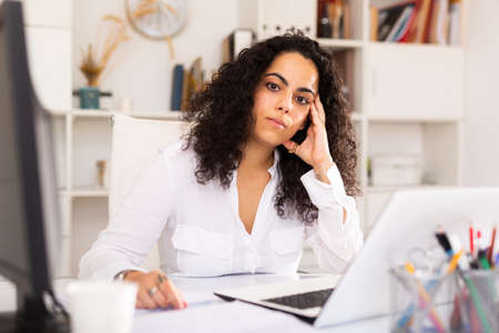 Upset young businesswoman working with documents