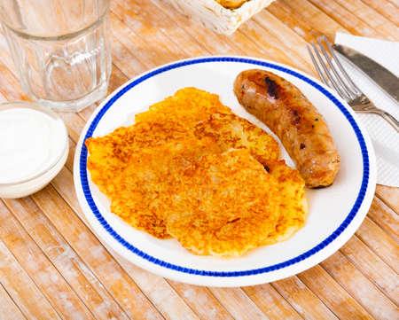 Potato pancakes with sausage and sour cream