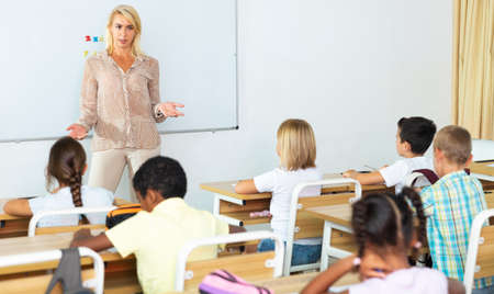 Woman teacher is giving interesting lecture for primary school students in classroom 版權商用圖片