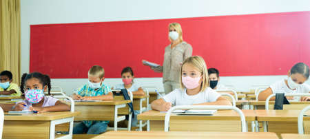 Preteen pupils with teacher in protective masks studying in classroom