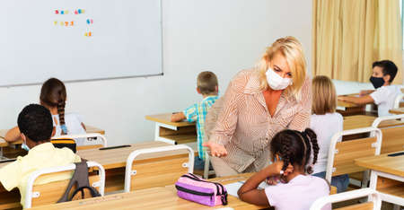Teacher woman in protective mask helping schoolkid during lesson