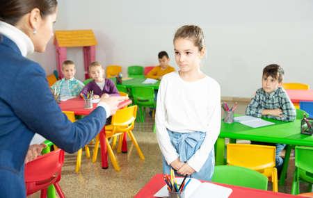 Upset schoolgirl listening reprimanding of teacher