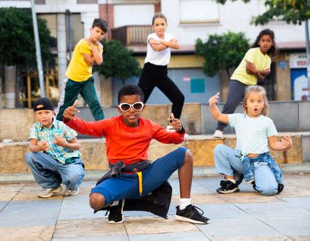 Preteen boys and girls breakdancers dancing on city street 免版税图像