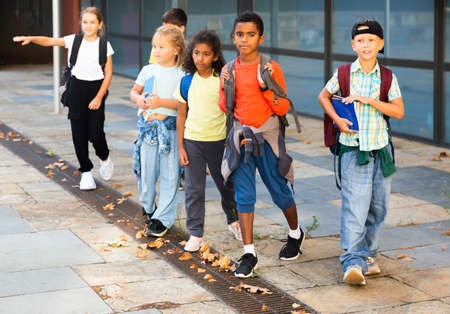 Smiling tweenagers walking outside school building on autumn day