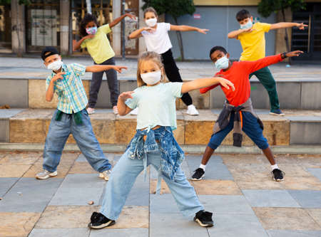 Preteen boys and girls breakdancers in masks dancing on city street