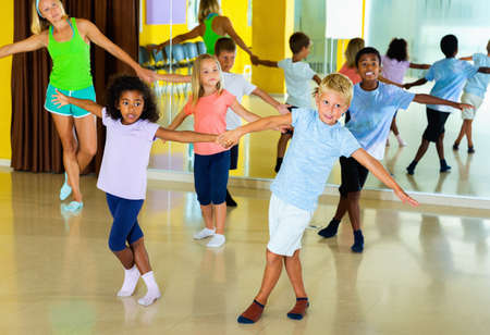 Group of children practicing vigorous jive movements in dance class with female coach