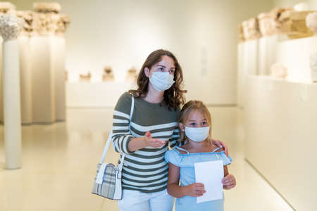 Mother and daughter in protective masks looking at paintings in halls of museum