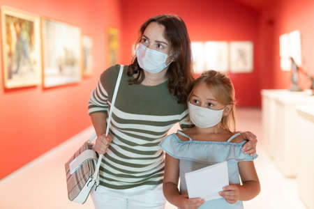Woman visitor with daughter in masks looking at painting