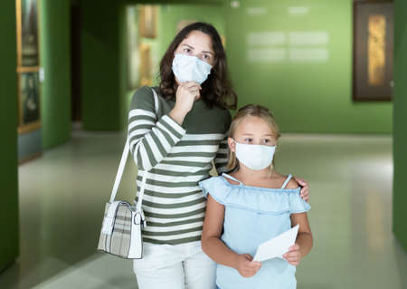 Woman with daughter in medical masks in museum of arts 免版税图像