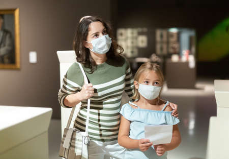 Woman with daughter in medical masks in museum of arts