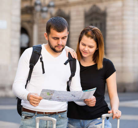 Portrait of young smiling couple with map