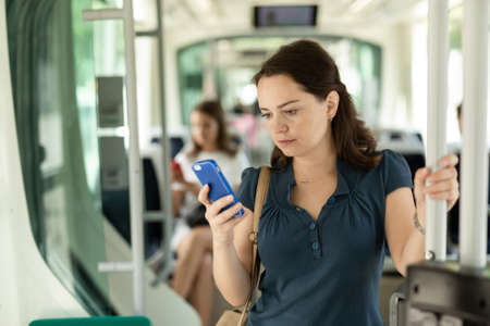 Woman using mobile phone in the cabin of a bus or tram