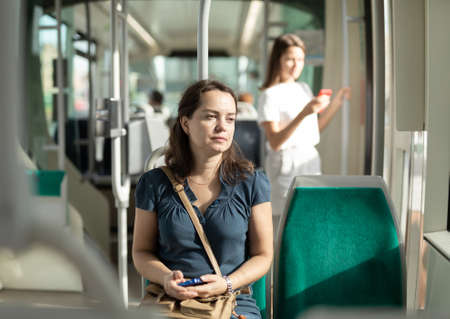 Positive woman reading from mobile phone screen in the cabin of bus or tram