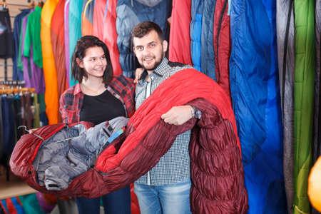 Ordinary couple examining various sleeping bags