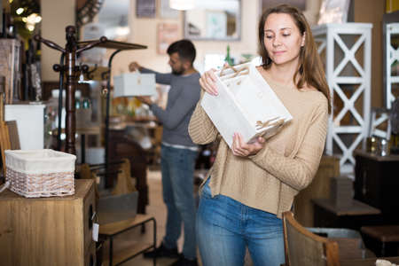 Girl choosing home decor elements in store Imagens