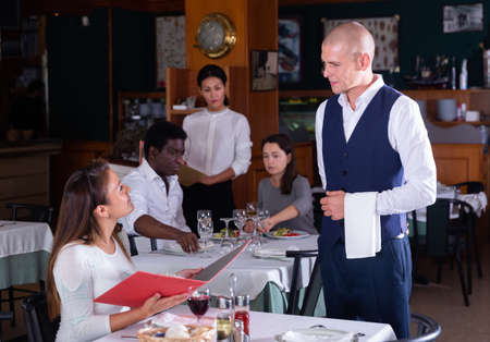 Hispanic woman holding menu and consulting with waiter in restaurant