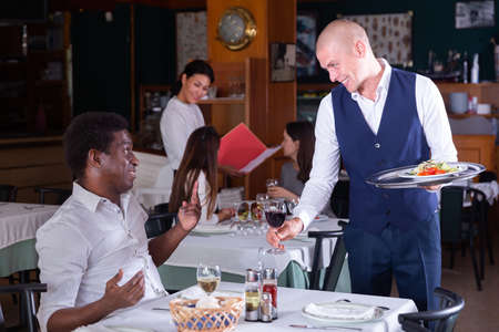 Friendly waiter serving cheerful African American in restaurant
