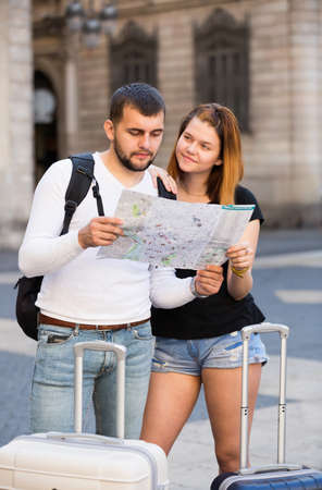 Cheerful couple traveling with map and package 免版税图像