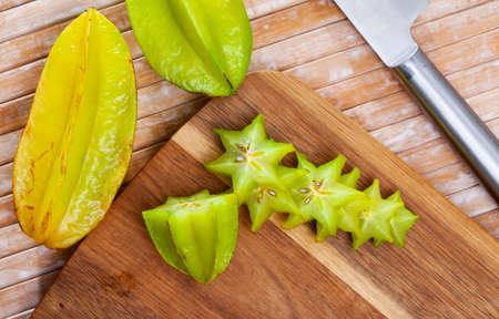 Whole and sliced star fruits on wooden surface