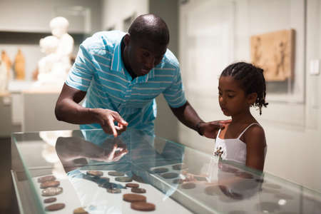 Father and daughter looking at stands with exhibits