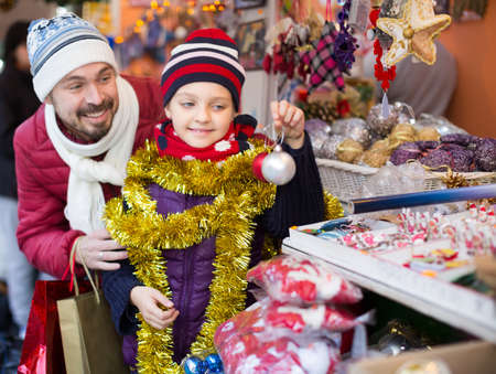 Happy man with small daughter with Christmas garlands