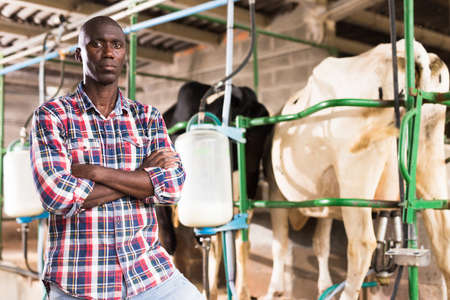 Portrait of farmer man staning near cow milking machines indoor at farm