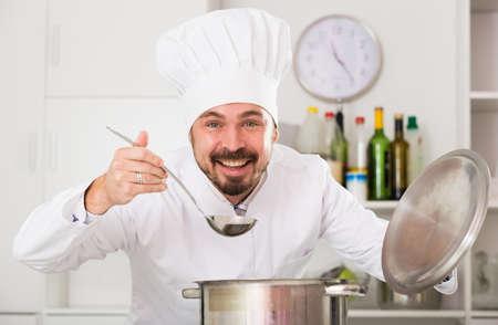 Male cook tasting food